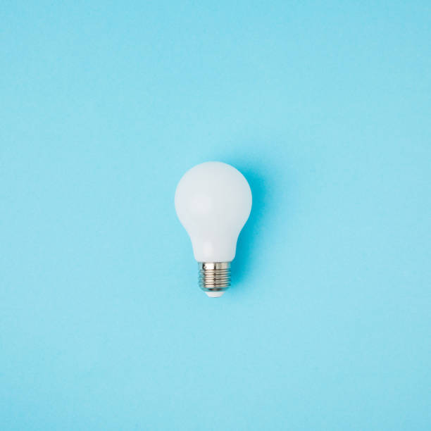 close up view of white light bulb isolated on blue - single object stock pictures, royalty-free photos & images