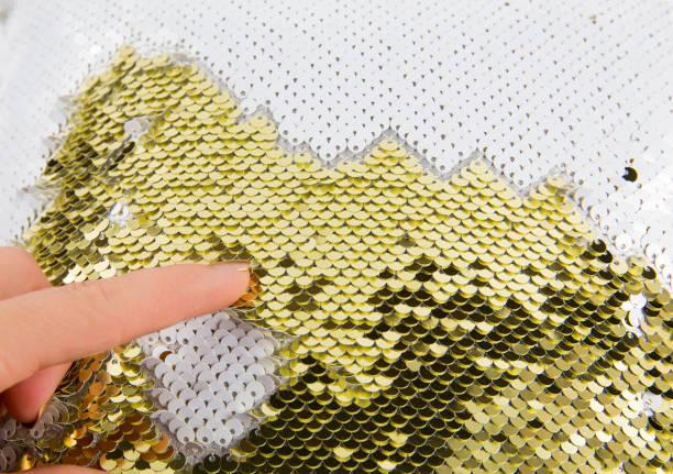 nahaufnahme der frau fingerspiel mit gold und weißen schimmer pailletten reversiblen stoff. kunsthandwerk material-ideenkonzept und großer stress erleben die geschäftige urlaubszeit. - verwandlungskissen stock-fotos und bilder