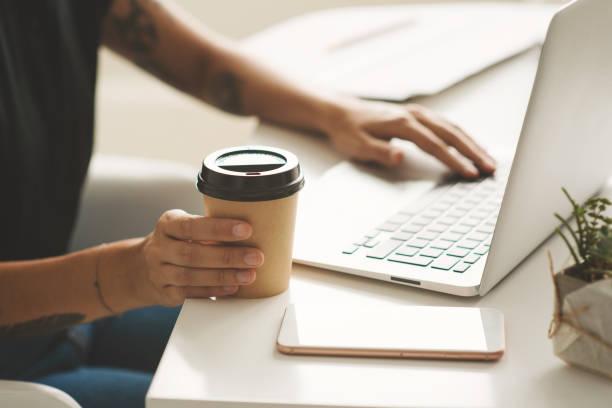 nahaufnahme der frau hände mit laptop am arbeitsplatz im büro - kaffeetasse tattoo stock-fotos und bilder