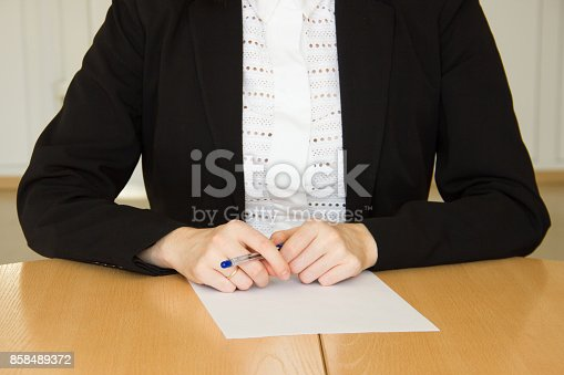 Close up view of woman at table, her hands with pen and paper. HR manager or agreement signing concept