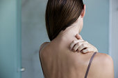 istock Close up view of woman scratching her neck. 1267751335