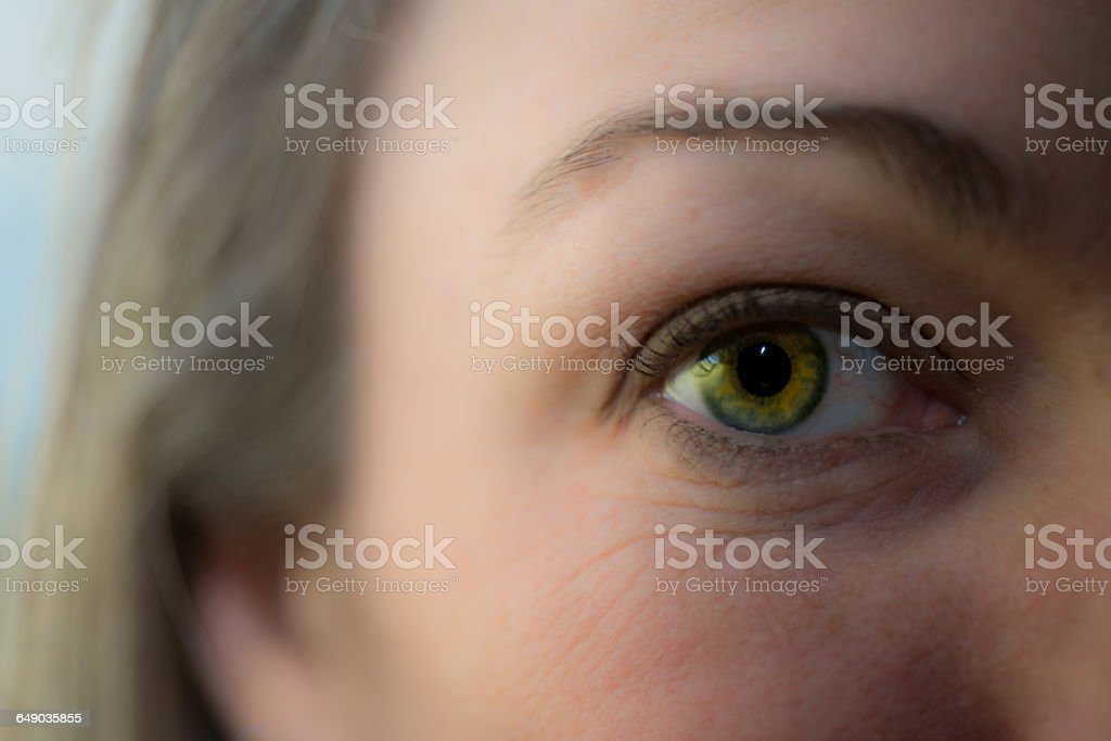 Close up view of woman's eye, looking at camera stock photo