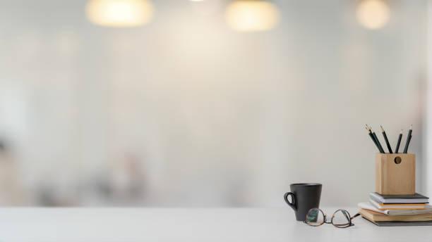 vista de perto do espaço de trabalho com papelaria, copos e xícara de café na mesa branca com fundo desfocado - escrivaninha - fotografias e filmes do acervo