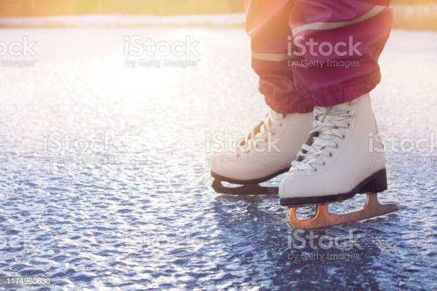 Photo of Close up view of young 4 year old girl wearing white figure skates, skating on frozen lake in nature outdoors on cold sunny winter day. Hobby concept.