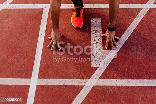 close up view of young muscular athlete is at the start of the race tracks line at the stadium. Sports concept