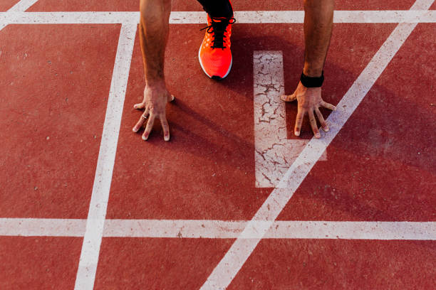 close up view of young muscular athlete is at the start of the race tracks line at the stadium. Sports concept stock photo