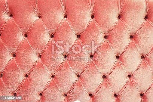 Close up view on bright textile of sofa wtih rivets