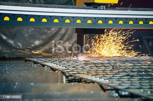 Close up view on CNC plasma cutting machine. CNC gas cutting metal sheet. Laser or plasma cutting technology. Selective focus and noise grain. sparks. factory concept with copy space