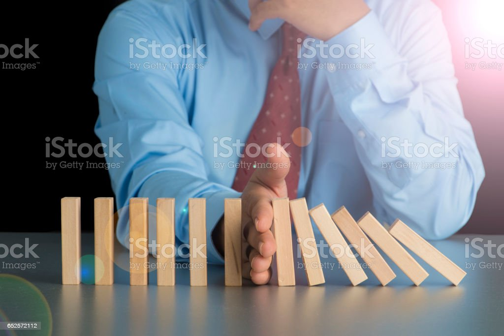 Close up view on hand of business woman stopping falling blocks on table for concept about taking responsibility with lens flare effect stock photo