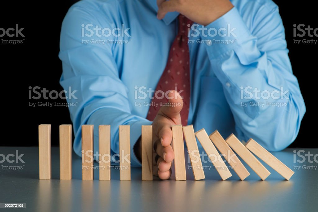 Close up view on hand of businessman stopping falling blocks on table for concept about taking responsibility. stock photo