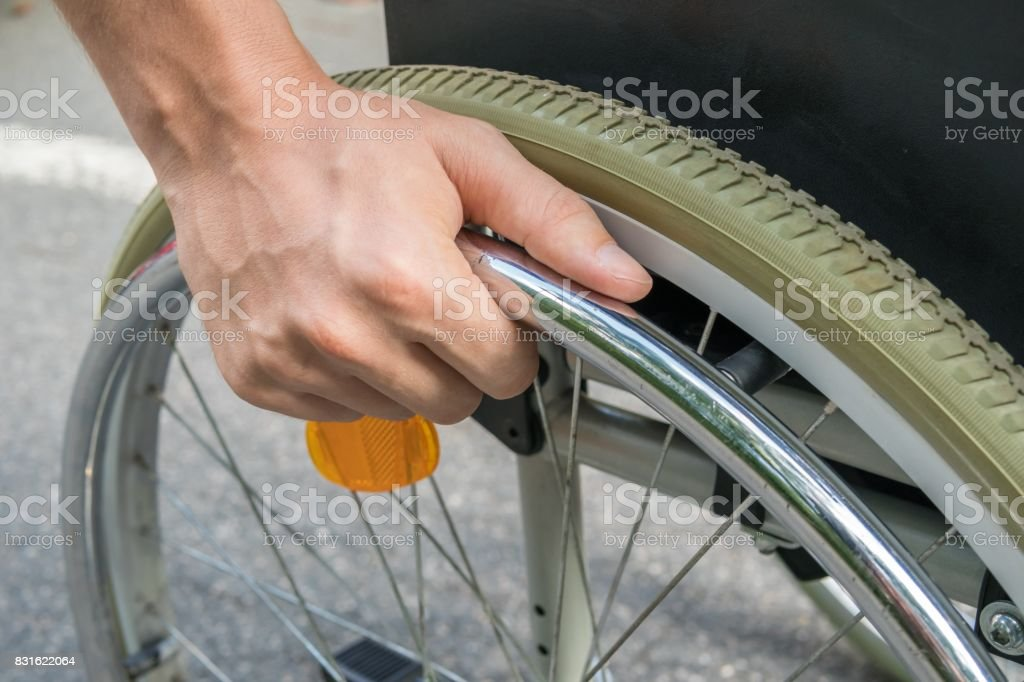 Close up view on hand of handicapped man on wheelchair. stock photo