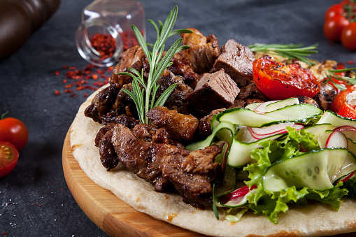 Close up view on tasty grilled meat with vegetables on georgian pita. shashlik or barbecue meat on pita. Shish kebab, traditional georgian cuisine food. Copy space for design. Dark background