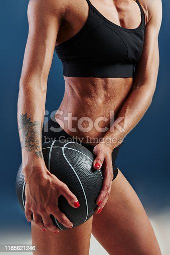 676005390istockphoto Close up view. Redhead female bodybuilder is in the studio on blue background 1185621246