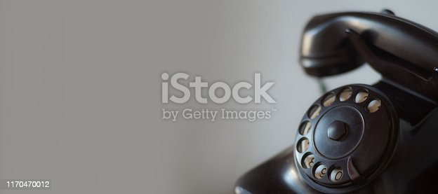 Vintage black and old telephone with retro style lighting and large copy space.