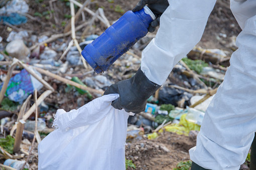 Close up Volunteer man in white protective clothing collects garbage