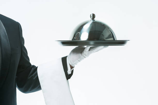 Close up waiter hand with tray and metal cloche lid cover Close up waiter hand with tray and metal cloche lid cover. the concept of the best service and suggestions covering stock pictures, royalty-free photos & images