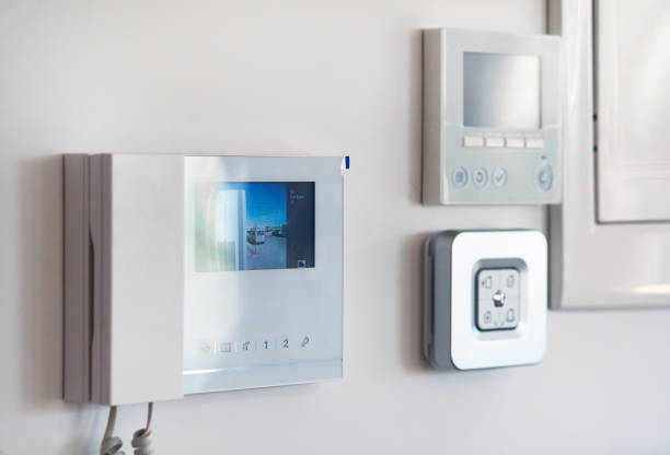 Close up wall with security alarm and video intercom Concept of smart modern luxury wealthy home. On white wall home security alarm and video intercom with street view talkback or doorphone voice communications system close up, no people home automation stock pictures, royalty-free photos & images
