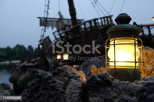Blurred dark pirate ship wreckage and sky background. Evening time