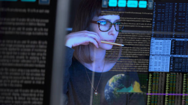 Close up watching Stock image of a beautiful young woman studying a see through computer screen & contemplating. computer equipment stock pictures, royalty-free photos & images