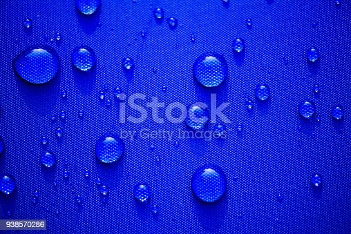 istock Close up Water drops pattern over a blue waterproof cloth background. World Water Day concept. 938570286