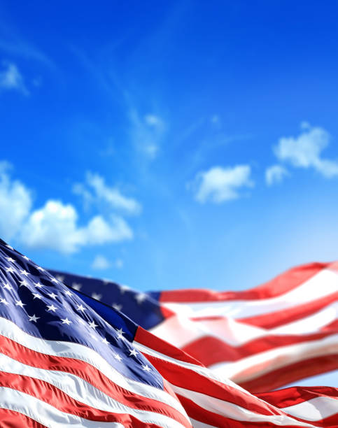 close up waving American flags over sunny cloudy blue sky stock photo