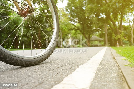 Close up wheel of bicycle in the park with evening light
