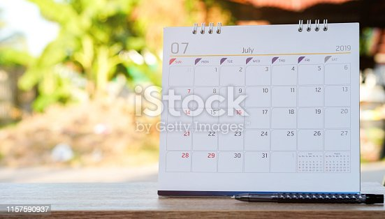1027407218 istock photo close up white color calendar july 2019 standing on wood table at outside for make appointment or remind important date , workplace with object concept 1157590937