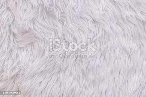 Close up white shaggy artificial fur texture or carpet for background.