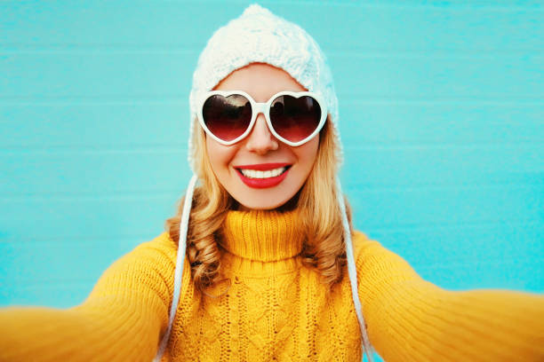 Close up winter portrait of happy smiling woman stretching hand for taking selfie wearing yellow knitted sweater and white hat, heart shaped sunglasses on blue wall background stock photo