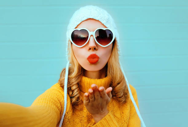 Close up winter portrait pretty woman blowing red lips sending sweet air kiss stretching hand for taking selfie wearing yellow knitted sweater, white hat, heart shaped sunglasses on blue background stock photo