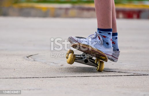Close up with a young man's feet on a skateboard.