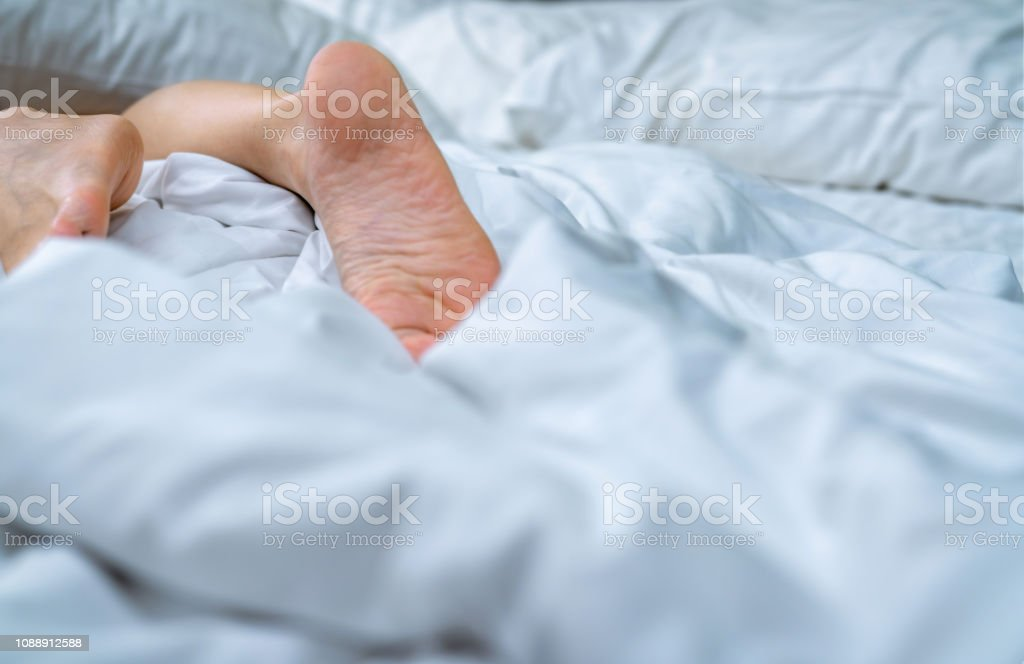 Close up woman bare feet on the bed over white blanket and bed sheet...