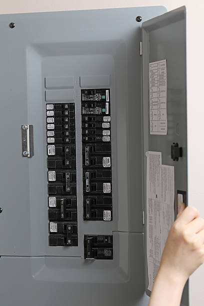close up woman checking electricity distribution box - fuse box stock photos and pictures