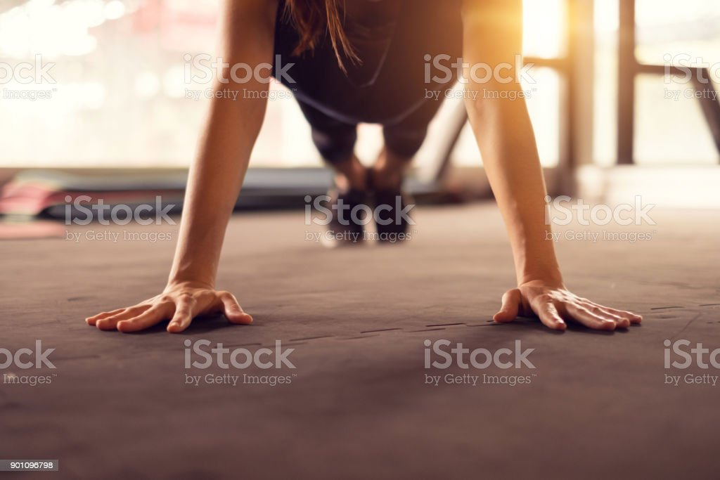 Close up woman hand doing push ups exercise in a gym in morning, sunlight effect.