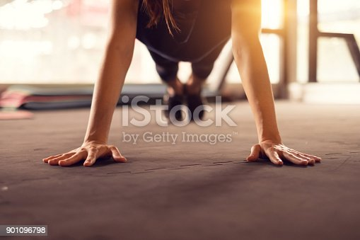 istock Close up woman hand doing push ups exercise in a gym in morning, sunlight effect. 901096798