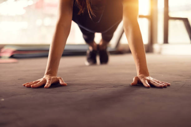 Close up woman hand doing push ups exercise in a gym in morning, sunlight effect. stock photo