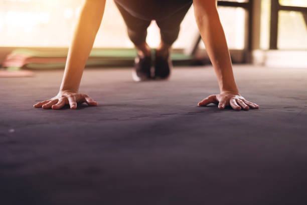close up woman hand doing push ups exercise in a gym in morning, sunlight effect. - peso mosca foto e immagini stock