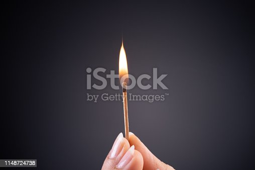 Close up woman hand holding a burning match.