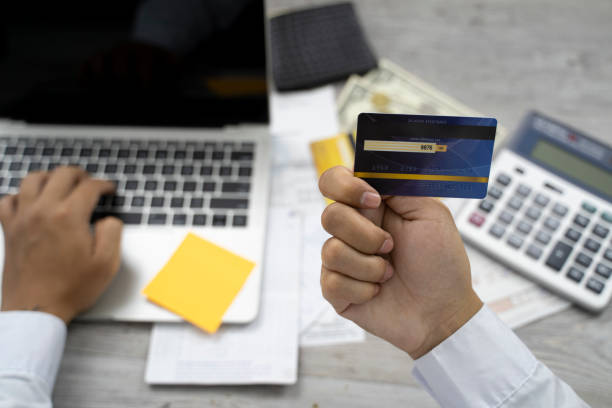 Close up woman hand holding credit card and paying on laptop. Shopping online concept. Image. stock photo