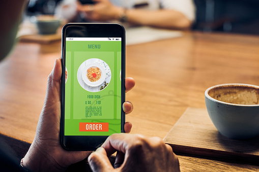 Close up woman hand holding food online mobile apps with hot coffee cup on table sitting at coffee shop,online order concept.