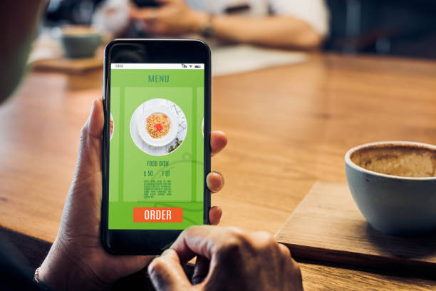stäng upp kvinna hand hålla mat online mobilappar med varma kaffekoppen på bordet sitter på kafé, beställning online koncept. - on demand bildbanksfoton och bilder