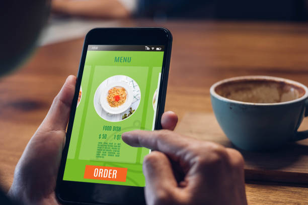 Close up woman hand holding food online mobile apps with hot coffee cup on table sitting at coffee shop,online order concept stock photo