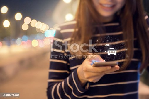 istock Close up woman hand orders a taxi from his mobile smartphone application. 965004050