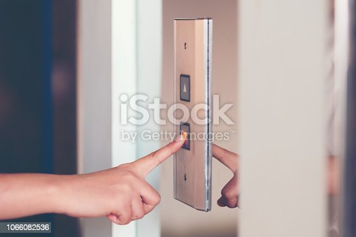 istock Close up woman hand press a up button of elevator inside the building for lower level floor. 1066082536