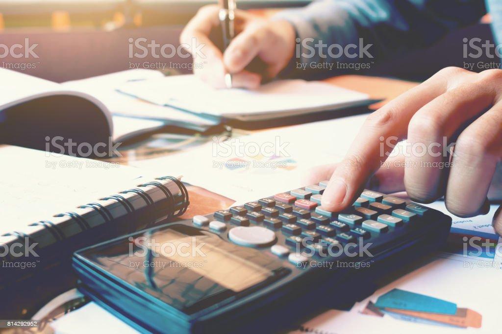 Nahaufnahme von Frau Hand drücken Rechner und Finanzen zu Hause Amt mit Schreiben zu tun beachten Sie Bericht über Notebook. – Foto