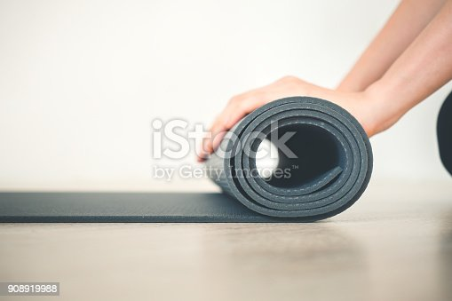 istock close up woman hand rolling yoga mat in yoga class work out 908919988