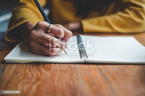 istock Close up woman hand writing on notebook 1035462384