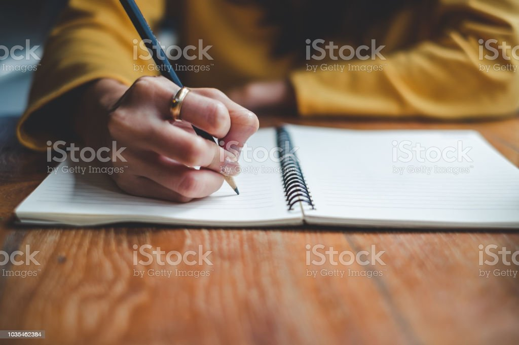 Close up woman hand writing on notebook stock photo
