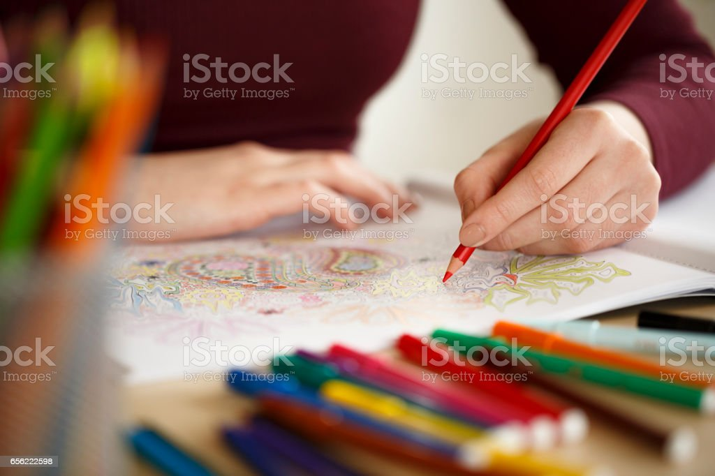 Close Up Woman Hands Coloring An Adult Coloring Book stock photo