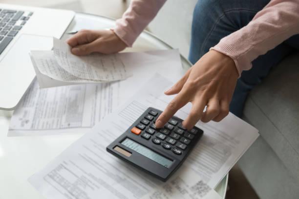 cerrar mano de mujer sosteniendo recibo de cálculo de los gastos de la empresa - deuda fotografías e imágenes de stock